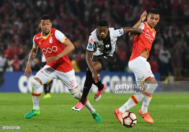 Colombia's Santa Fe Juan Daniel Roa and Yeison Stiven Gordillo vie for the ball with Brazil's Santos Bruno Henrique during their Copa Libertadores...