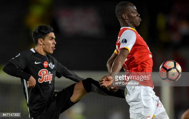 Colombia's Santa Fe player Baldomero Perlaza vies for the ball with Paraguay's Libertad Jesus Medina during their Copa Sudamericana football match at...