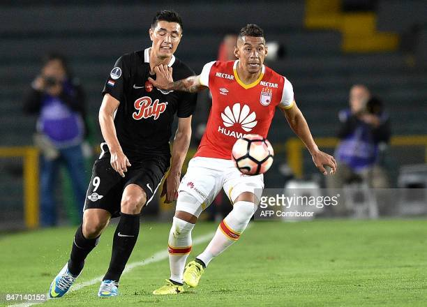 Colombia's Santa Fe William Tesillo vies for the ball with Paraguay's Libertad player Oscar Cardozo during their Copa Sudamericana football match at...