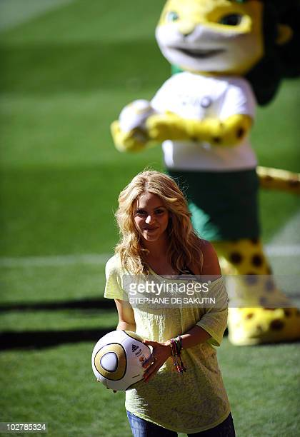 Colombia's singer Shakira holding the Jo'bulani football that will be used for the final of the tournament stands next the official mascot Zakumi...