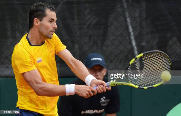 Colombia's tennis player Santiago Giraldo returns the ball to Chile's Christian Garin during their Davis Cup match in Medellin Colombia on April 9...