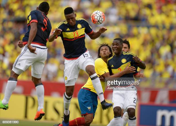 Colombia's Yerry Mina and Miguel Borja jump for the ball during their 2018 FIFA World Cup qualifier football match in Quito on March 28 2017 / AFP...