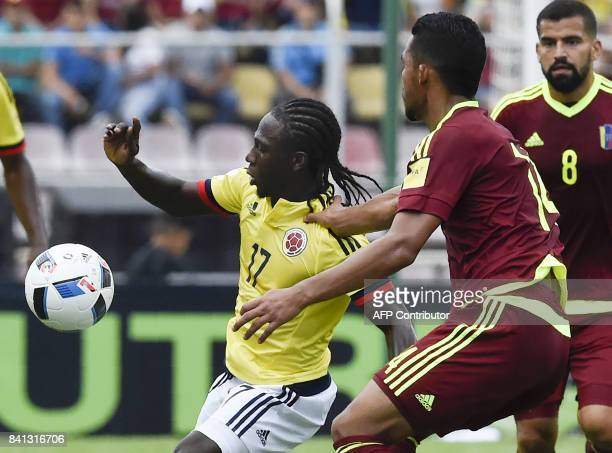 Colombia's Yimmi Chara and Venezuela's Yangel Herrera vie for the ball during their 2018 World Cup qualifier football match in San Cristobal...