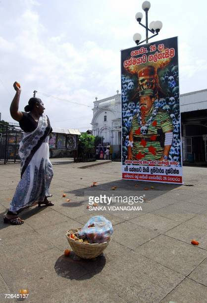 A Sri Lankan woman throws a tomato towards a billboard featuring an image of Liberation Tigers of Tamil Eelam Leader Velupillai Prabhakaran outside...