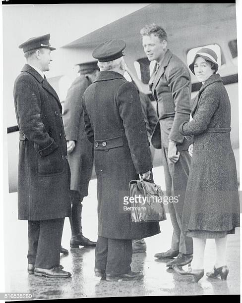 Colonel and Mrs Charles A Lindbergh being greeted by two customs officers assigned to expedite their clearance through the airport as they landed in...
