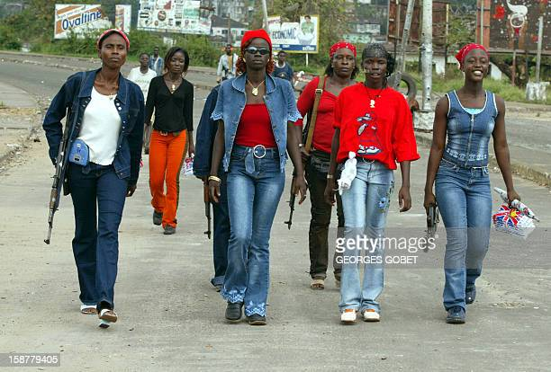 Colonel 'Black Diamond' is flanked by her women bodyguards members of the LURD 09 August 2003 as they return from a patrol around the bridge '...