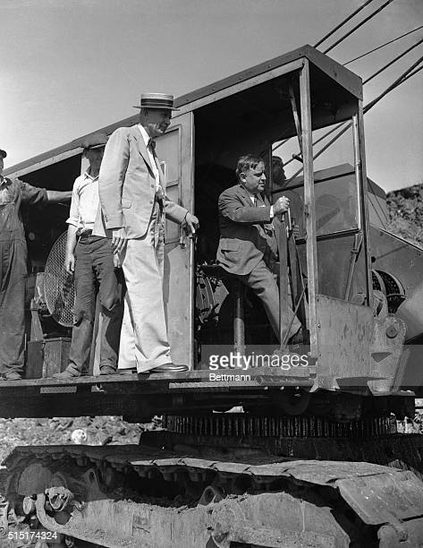 Colonel Brehon B Somervell looks on as Mayor Fiorella La Guardia of New York manipulates the controls of a steam shovel and scoops up the first load...