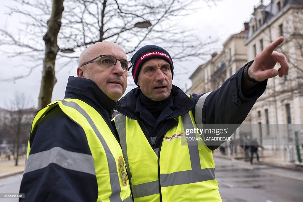 Colonel Eric Faure (L), president of the National Firefighters Federation (SNSPF - Federation Nationale des Sapeurs Pompiers de France) and a firefighter (R) march in Valence central eastern France, to protest against the closure of 19 emergency services and fire centers, on February 13, 2016. / AFP / ROMAIN LAFABREGUE