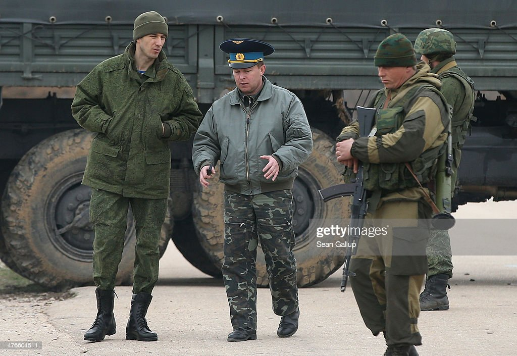Colonel Yuli Mamchor (C), commander of the Ukrainian military garrison at the Belbek airbasespeaks with troops under Russian command occupying the Belbek airbase after Mamchor led over 100 of his unarmed, Ukrainian soldiers to confront the occupiers at the airfield in Crimea on March 4, 2014 in Lubimovka, Ukraine. The Ukrainians are stationed at their garrison nearby, and after spending a tense night anticipating a Russian attack following the expiration of a Russian deadline to surrender, in which family members of troops spent the night at the garrison gate in support of the soldiers, Mamchor announced his bold plan this morning to retake the airfield by confronting the Russian-lead soldiers unarmed. The Russian-lead troops fired their weapons into the air but then granted Mamchor the beginning of negotiations with their commander. Russian-lead troops have blockaded a number of Ukrainian military bases across Crimea.