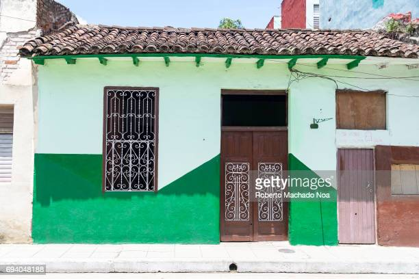 Colonial architecture house with multiple brown doors and windows and tiled roof