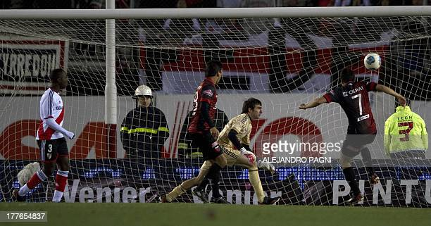 Colon's forward Facundo Curuchet socres the team's first goal against River Plate during their Argentine First Division football match at the...