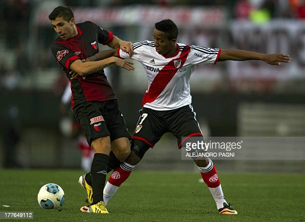 Colon's midfielder Lucas Mugni vies for the ball with River Plate's midfielder Carlos Carbonero during their Argentine First Division football match...