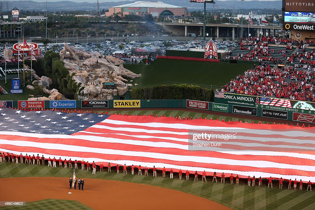 A color guard and a giant American flag are on the field during the national anthem before the Kansas City Royals and the Los Angeles Angels of...