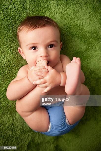 Image en couleur de bébé garçon allongé sur une couverture duveteuse vert