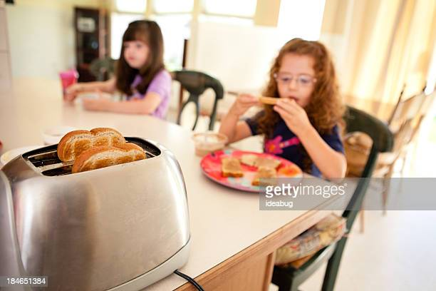 Color Image of Sisters Eating in Their Kitchen at Home
