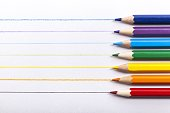 Colored pencils arranged in a row on white wooden background