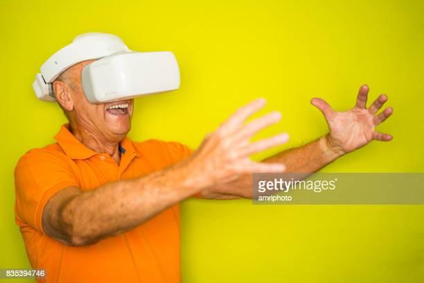 Surtension de couleur pour élégant Seniors - senior homme avec VR googles et bras tendus
