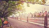 Color toned picture of a promenade in Roosevelt Island with view of Manhattan, focus on buildings, New York City, USA.