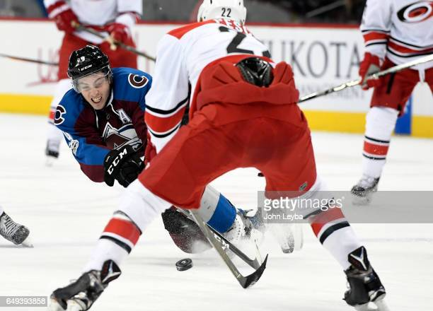 Colorado Avalanche center Matt Duchene falls to the ice as she skates after the puck in from of Carolina Hurricanes defenseman Brett Pesce during the...