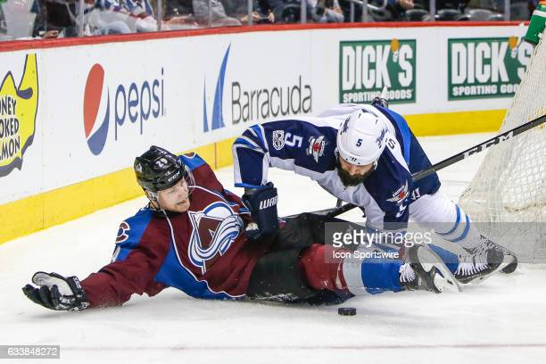 Colorado Avalanche Center Nathan MacKinnon falls to the ice after being pushed by Winnipeg Jets Defenseman Mark Stuart during the Winnipeg Jets and...