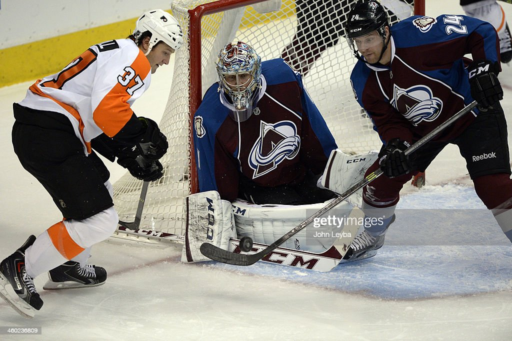 Colorado Avalanche right wing MarcAndre Cliche pokes the puck out as Philadelphia Flyers left wing Jay Rosehill and Colorado Avalanche goalie Semyon...