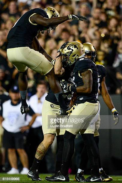 Colorado Buffaloes defensive back Afolabi Laguda leaps in and celebrates with defensive back Tedric Thompson and defensive back Ahkello Witherspoon...