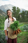 USA, Colorado, Carbondale, Portrait of woman holding carrots in field