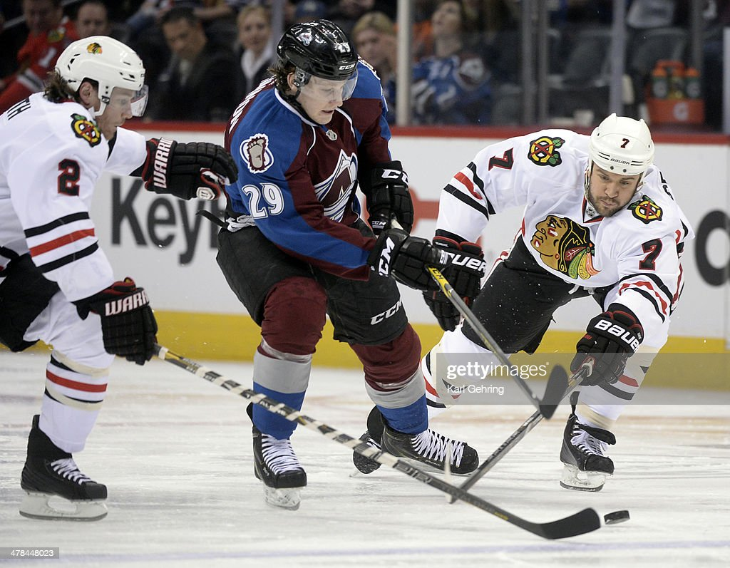Colorado center Nathan MacKinnon (29) tried to squeeze the puck between Duncan Keith (2) and Brent Seabrook (7) in the first period. The Colorado Avalanche hosted the Chicago Blackhawks at the Pepsi Center Wednesday night, March 12, 2014 in Denver, Colorado.