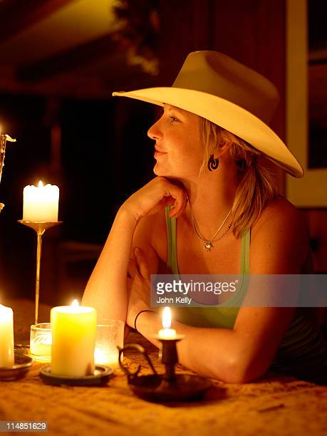 USA, Colorado, Cowgirl sitting at table with candles