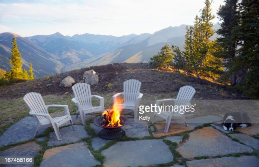 USA, Colorado, Dog lying down by fire pit and four empty chairs : Stock Photo