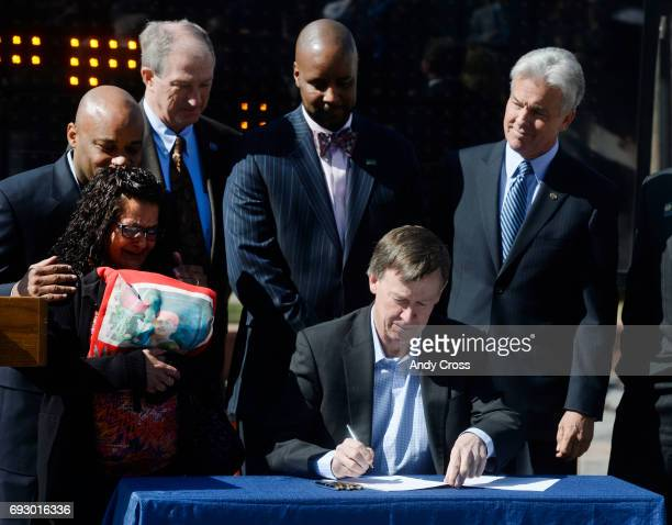 Colorado Governor John Hickenlooper bottom center signs Colorado HB141191 into law in front of the Colorado State Capitol Tuesday morning March 25...