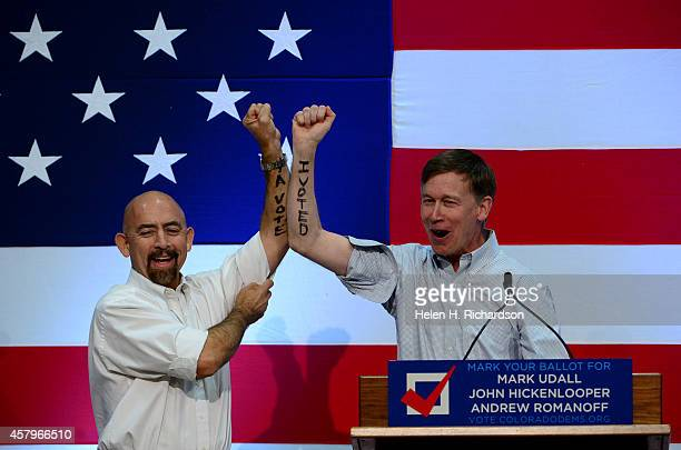Colorado governor John Hickenlooper right and Lt Governor Joe Garcia hold up their arms to show that they have already voted to a packed audience...