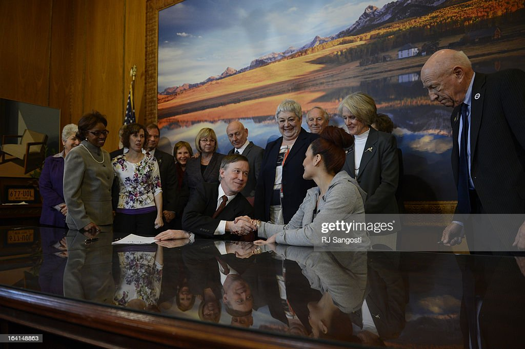Colorado Governor John Hickenlooper shacks the hand of Karina Vargas, right, who was paralyzed from a shooting outside Aurora Central High School, after the Governor sign three gun control measures in his office at the state capitol, March, 20, 2013.