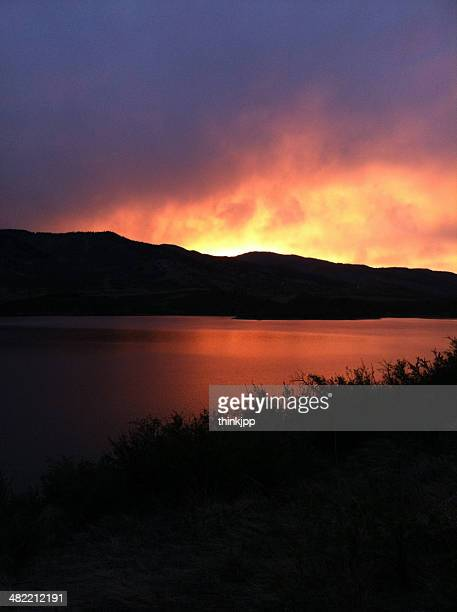 USA, Colorado, Larimer County, Fort Collins, Sunset in mountains across peaceful lake