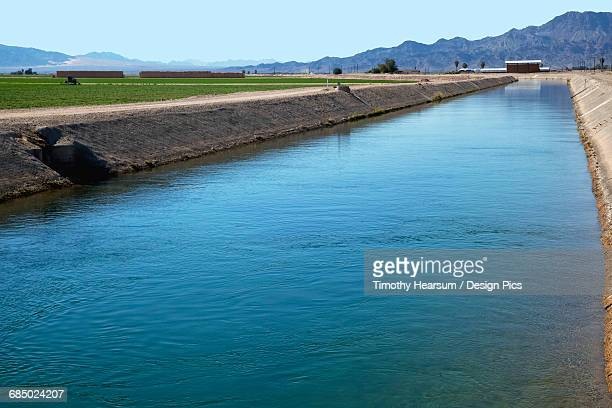Colorado River Irrigation Canal is seen with alfalfa, bales, farm buildings and mountains in the background, near Ehrenburg