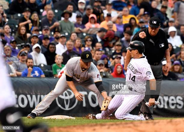 Colorado Rockies catcher Tony Wolters is tagged out at third base by Pittsburgh Pirates third baseman David Freese on a throw from the catcher...