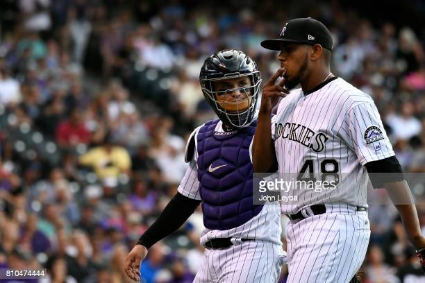 Colorado Rockies catcher Tony Wolters talks with starting pitcher German Marquez as they come off the field in the second inning against the Chicago...