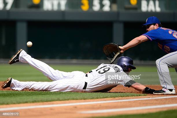 Colorado Rockies center fielder Charlie Blackmon slides into first base New York Mets second baseman Daniel Murphy waits to grab the pass from New...