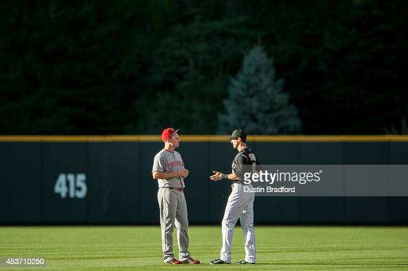 Colorado Rockies center fielder Drew Stubbs talks to former teammate Cincinnati Reds right fielder Jay Bruce during a delay in the start of a game at...