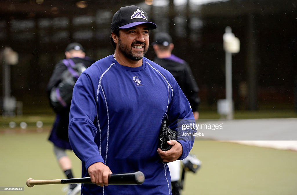 Colorado Rockies coach Vinny Castilla heads in doors as the team hits in the cages on a rainy day during workouts on day 10 of spring training March...