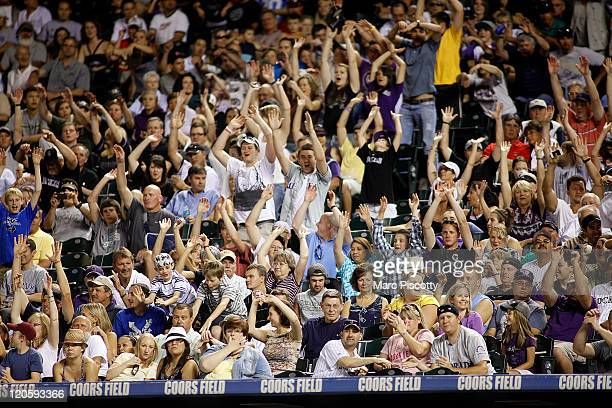 Colorado Rockies fans participate in 'the wave' as it makes its way around the ballpark during a game against the Washington Nationals at Coors Field...