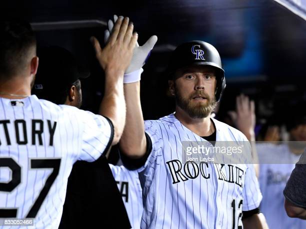 Colorado Rockies first baseman Mark Reynolds high fives shortstop Trevor Story in the dugout after his homer in the fourth inning against the Atlanta...