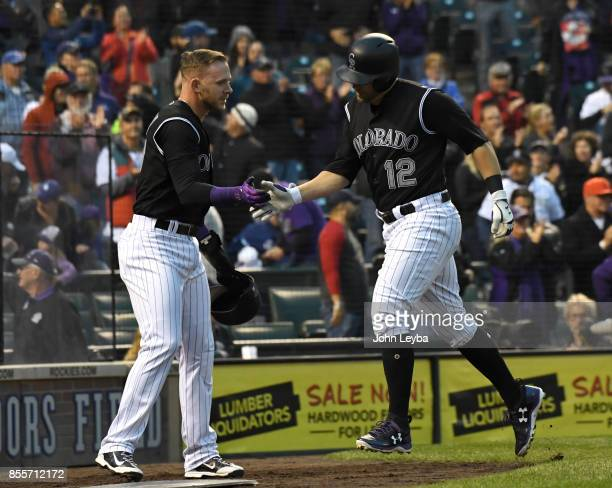 Colorado Rockies first baseman Mark Reynolds high fives shortstop Trevor Story after hitting his hits his 30th homer in the first inning against the...