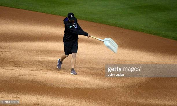 Colorado Rockies grounds crew throws down diamond dust to dry the infield between innings against the Washington Nationals on April 25 2017 in Denver...