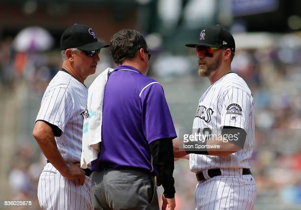 Colorado Rockies Manager Bud Black and the Rockies trainer check on Rockies Infielder Mark Reynolds during a regular season MLB game between the...