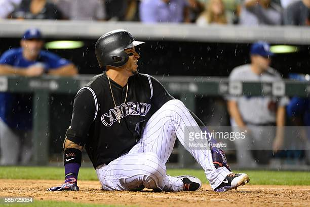 Colorado Rockies outfielder Carlos Gonzalez rolls his ankle during an atbat in the seventh inning of the game against the Los Angeles Dodgers at...