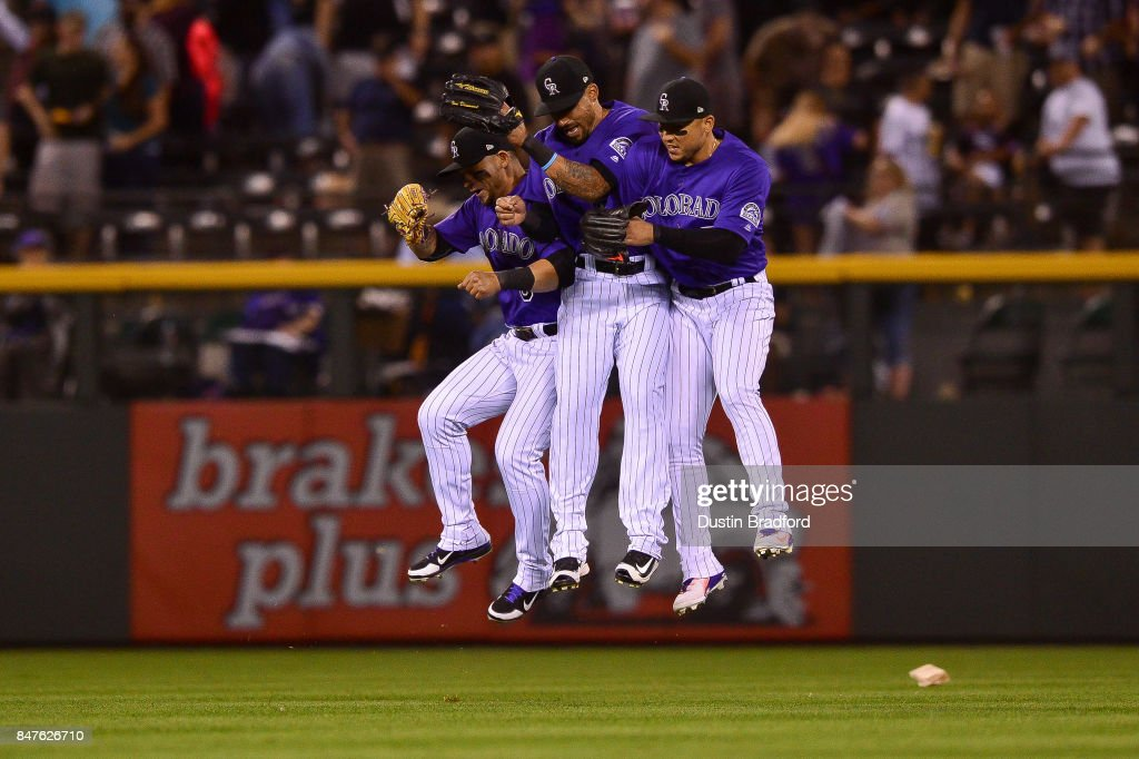 Colorado Rockies outfielders, from left, Gerardo Parra #8, Ian Desmond #20, and Carlos Gonzalez #5 celebrate after a 6-1 win over the San Diego Padres at Coors Field on September 15, 2017 in Denver, Colorado.