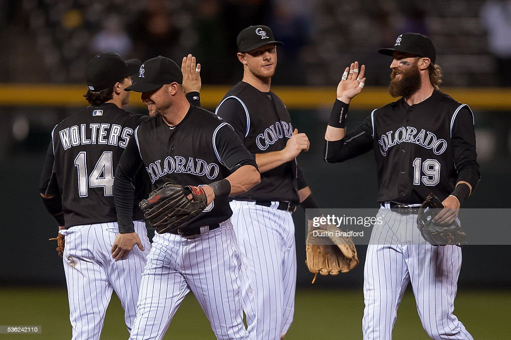 Colorado Rockies players, from left, Tony Wolters #14, Ryan Raburn #6, DJ LeMahieu #9, and Charlie Blackmon #19 celebrate after a 17-4 win over the Cincinnati Reds at Coors Field on May 31, 2016 in Denver, Colorado.
