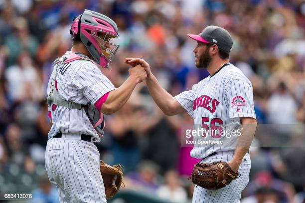 Colorado Rockies relief pitcher Greg Holland celebrates the win with Dustin Garneau after pitching in the ninth inning during a regular season Major...