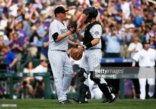 Colorado Rockies Relief Pitcher Jake McGee and Catcher Dustin Garneau celebrate a win at the end of a regular season MLB game between the Colorado...